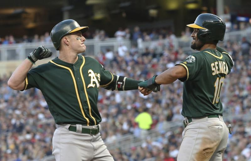 Oakland Athletics' Mark Canha, left, and Marcus Semien celebrate Canha's two-run home run off Minnesota Twins pitcher Zack Littell in the seventh inning of a baseball game Saturday, July 20, 2019, in Minneapolis. The Athletics won 5-4. (AP Photo/Jim Mone)