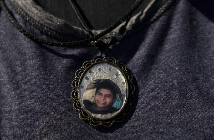 A woman wears a photograph of a missing person as she joins the Sixth National Search Brigade for disappeared persons on the outskirts of Cuautla, Mexico, Tuesday, Oct. 12, 2021. The government's registry of Mexico's missing has grown more than 20% in the past year and now approaches 100,000. (AP Photo/Fernando Llano)
