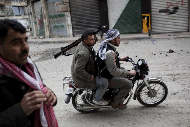 <p>Free Syrian Army fighters ride a motorbike to approach Syrian Army tanks in Idlib, northern Syria, on March 11, 2012. (Photo: Rodrigo Abd/AP) </p>