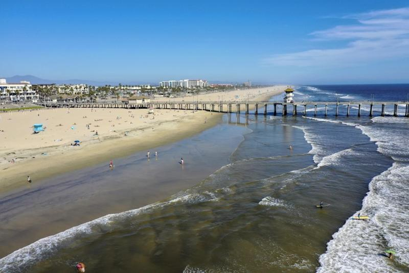 HUNTINTON BEACH, CA -- WEDNESDAY, APRIL 22, 2020: An aerial view of beach-goers enjoying warm summer-like weather amid state and city social distancing regulations mandated by Gov. Newsom at the closed Huntington Beach pier in Huntington Beach, CA, on April 22, 2020. The Orange County officials have been debating whether to close beaches and trailheads during an upcoming heat wave after coastal residents raised concerns about out-of-towners descending on their communities in droves. (Allen J. Schaben / Los Angeles Times)