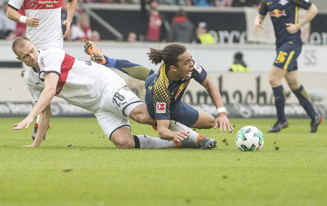 Stuttgart's Holger Badstuber, left, and Leipzig's goal Yussuf Poulsen fight for the ball during a German Bundesliga socer match between VfB Stuttgart and RB Leipzig in Stuttgart, Germany, Sunday, March 11, 2018. (Marjan Murat/dpa via AP)