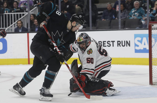 Chicago Blackhawks goaltender Corey Crawford (50) defends against a shot attempt by San Jose Sharks center Tomas Hertl during the first period of an NHL hockey game in San Jose, Calif., Thursday, March 28, 2019. (AP Photo/Jeff Chiu)