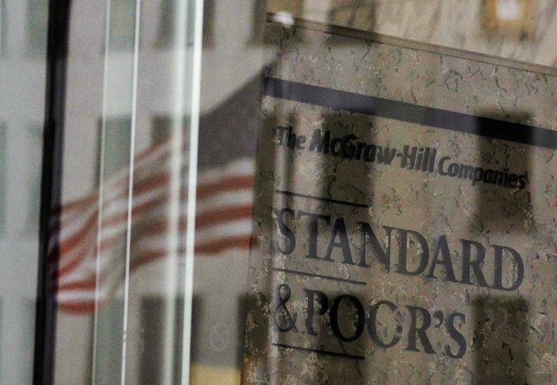 A U.S. flag is reflected in a window of the Standard and Poor's building in New York