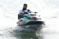 <p>DJ Khaled enjoys a ride on his colorful jet ski with his wife (not pictured) on Friday in Miami Beach.</p>