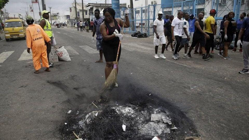 Volunteers sweep burned out tires on the roads in Lagos Saturday, Oct. 24, 2020. (AP Photo/Sunday Alamba)