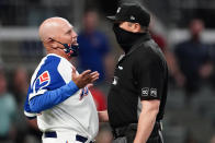 Atlanta Braves manager Brian Snitker, left, argues with umpire Lance Barrett, right, after the Philadelphia Phillies scored a run in the ninth inning of a baseball game Sunday, April 11, 2021, in Atlanta. (AP Photo/John Bazemore)