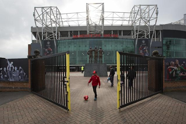 Members of the public stand outside Manchester United's Old Trafford Stadium after the club sacked manager David Moyes, Manchester, England, Tuesday, April 22, 2014. (AP Photo/Jon Super)