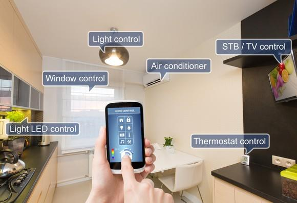 A person holding a smartphone that is remotely connected to devices in the room including a light and the thermostat.
