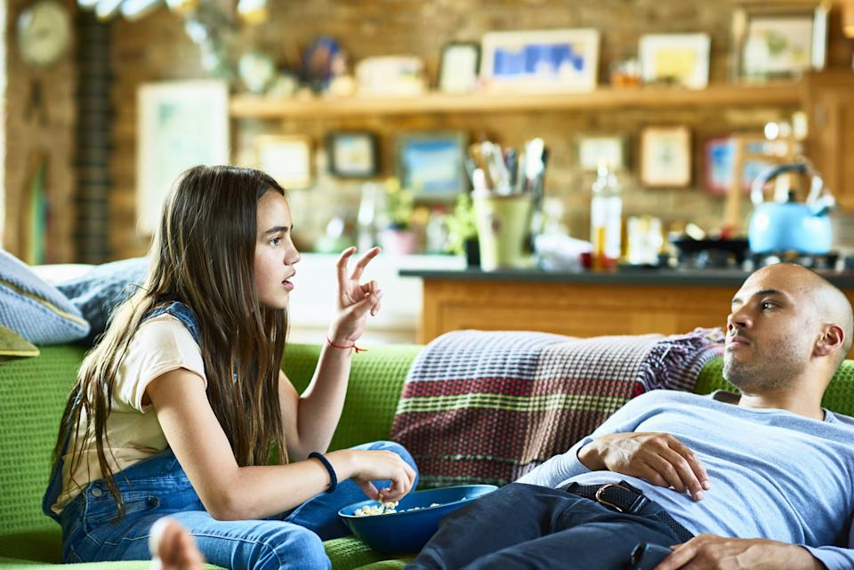 Father and daughter relaxing on green sofa in livingroom, eating popcorn and talking