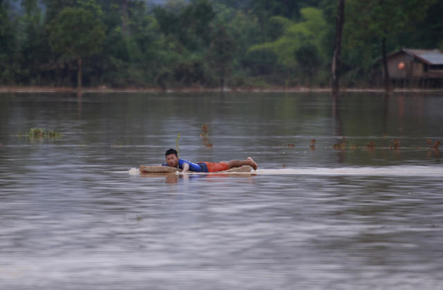 <p>A man swims with matress in flooded village in Sanamxay district, Attapeu province, Laos, Thursday, July 26, 2018. (Photo: Hau Dinh/AP) </p>