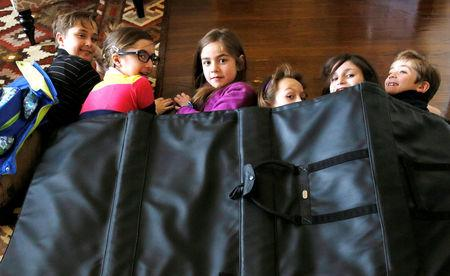 FILE PHOTO: Children demonstrate how they might take shelter in a school under a bulletproof blanket sold by Elite Sterling Security LLC (ESS) in Aurora, Colorado March 19, 2013. REUTERS/Rick Wilking/File Photo
