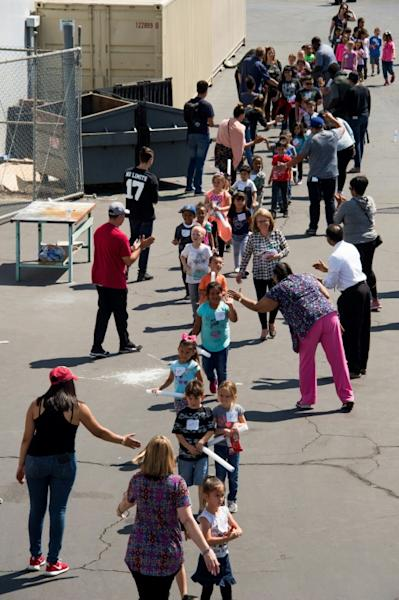 Children are on their way to be reunited with parents after a gunman entered a classroom and killed one woman and one student, before turning the gun on himself, at North Park Elementary School in San Bernardino, California, April 10 2017
