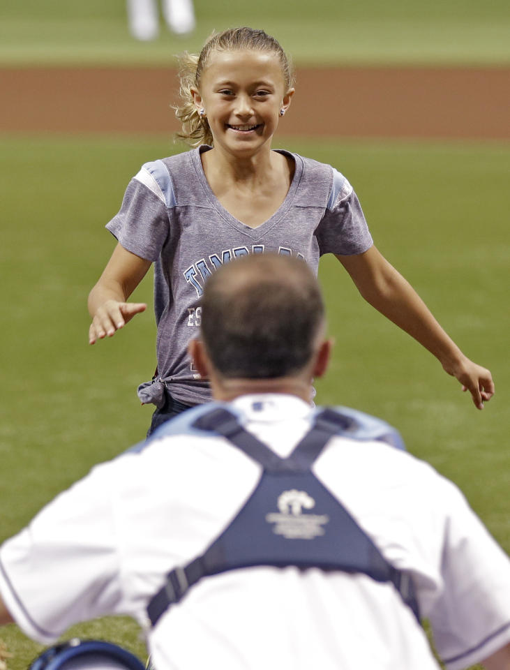 <p>Nine-year-old Alayna Adams runs to see her father, Army Lt. Col. William Adams, before a baseball game between the Tampa Bay Rays and the Boston Red Sox on Thursday, May 16, 2013, in St. Petersburg, Fla. Lt. Col. Adams, who had been stationed in Afghanistan, surprised his wife and daughter. (AP Photo/Chris O'Meara) </p>