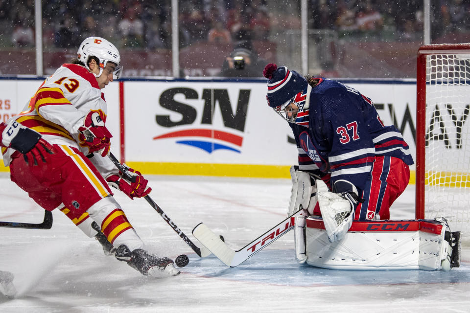 Winnipeg Jets goaltender Connor Hellebuyck (37) stops a shot from Calgary Flames' Johnny Gaudreau (13) during the first period of an NHL Heritage Classic in Regina, Canada, Saturday, Oct. 26, 2019. (Liam Richards/The Canadian Press via AP)