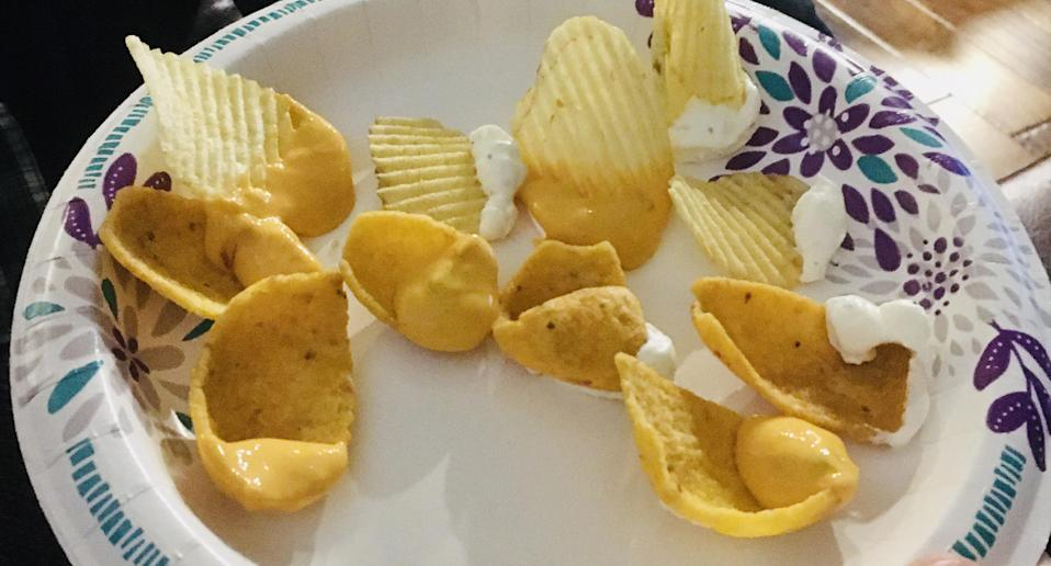 A plate full of chips that have been re loaded with dip