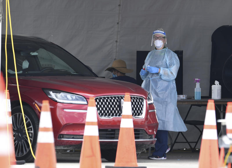 MIAMI GARDENS BEACH, FL - JULY 10: A Healthcare worker seen taking a swab sample from a driver at the Coronavirus (COVID-19) drive in testing site, set up in the parking lot of Hard Rock Stadium as Florida reports another record spike 11K in coronavirus cases, Floridaís Covid-19 surge shows the state's reopening plan is not working on July 10, 2020 in Miami Gardens, Florida. Credit: mpi04/MediaPunch /IPX