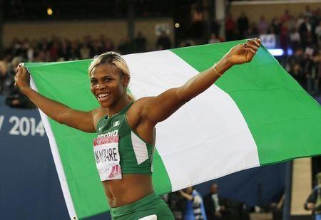 Nigeria's Blessing Okagbare carries her country's flag after winning the women's 200m final at the 2014 Commonwealth Games in Glasgow, Scotland, July 31, 2014. REUTERS/Suzanne Plunkett