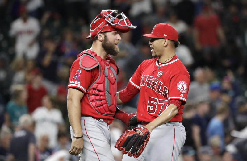Los Angeles Angels catcher Kevan Smith, left, shares congratulations with closing pitcher Hansel Robles after the team beat the Seattle Mariners in a baseball game Saturday, July 20, 2019, in Seattle. The Angels won 6-2. (AP Photo/Elaine Thompson)