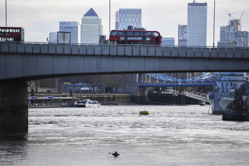 Buses and cars remain on London Bridge in London, Sunday Dec. 1, 2019, after it being closed to traffic and public after an attack on Friday. Authorities in Britain say the convicted terrorist who stabbed to death two people and wounded three others in a knife attack Friday had been let out of prison in an automatic release program. (AP Photo/Alberto Pezzali)