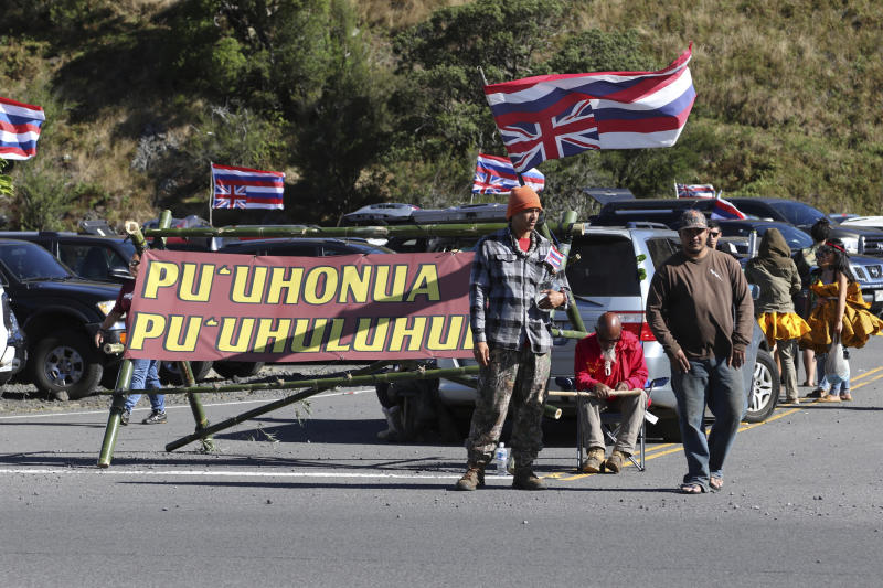 Native Hawaiian activists gather at the base of Hawaii's Mauna Kea, Sunday, July 14, 2019. Hundreds of demonstrators are gathered at the base of Hawaii's tallest mountain to protest the construction of a giant telescope on land that some Native Hawaiians consider sacred. State and local officials will try to close the road to the summit of Mauna Kea Monday morning to allow trucks carrying construction equipment to make their way to the top. Officials say anyone breaking the law will be prosecuted. Protestors have blocked the roadway during previous attempts to begin construction and have been arrested. (AP Photo/Caleb Jones)