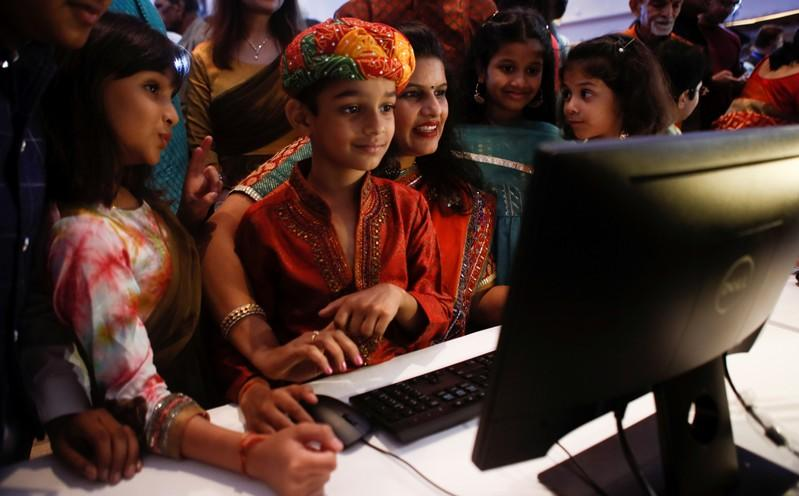 "A stockbroker and her family watch a terminal during a special ""muhurat"" trading session for Diwali, the Hindu festival of lights, at the Bombay Stock Exchange (BSE) in Mumbai"