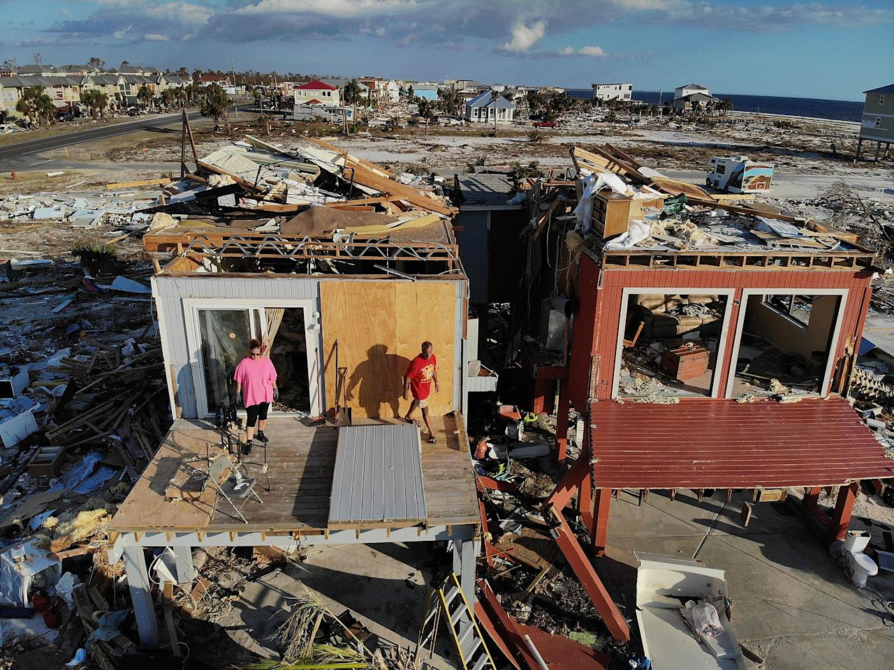 <p>Bela (L) and Jaques Sebastiao begin the process of cleaning up their home after it was heavily damaged by Hurricane Michael, on Oct. 17, 2018, in Mexico Beach, Fla. (Photo: Joe Raedle/Getty Images) </p>