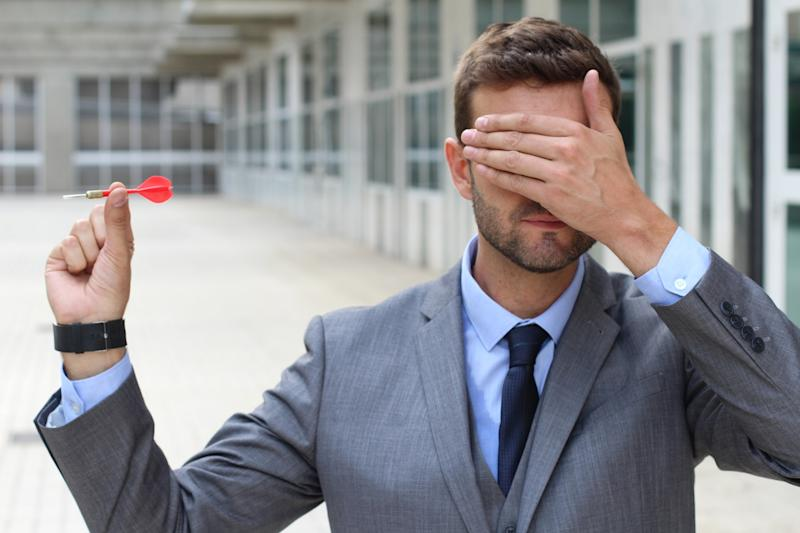 Man in a suit covering his eyes while holding a red dart.
