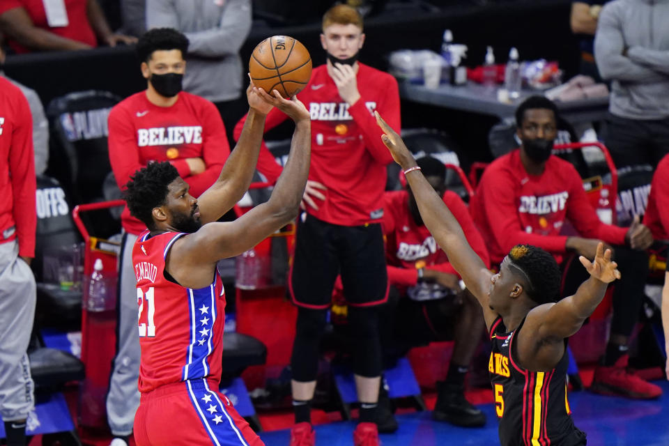 Philadelphia 76ers' Joel Embiid, left, goes up for shot against Atlanta Hawks' Clint Capela during the second half of Game 1 of a second-round NBA basketball playoff series, Sunday, June 6, 2021, in Philadelphia. (AP Photo/Matt Slocum)