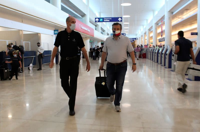 U.S. Senator Ted Cruz (R-TX) walks along an unidentified person at the Cancun International Airport before boarding his plane back to the U.S., in Cancun