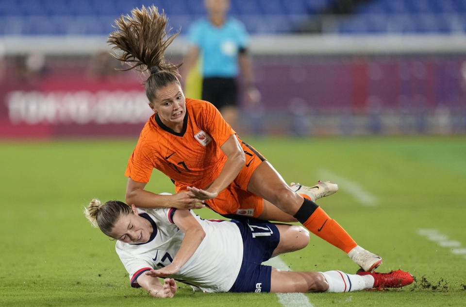 United States' Abby Dahlkemper, left, and Netherlands' Lieke Martens fall while fighting for the ball during a women's quarterfinal soccer match at the 2020 Summer Olympics, Friday, July 30, 2021, in Yokohama, Japan. (AP Photo/Silvia Izquierdo)