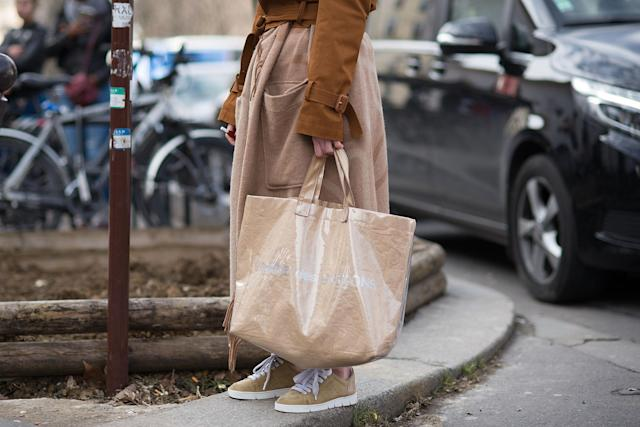 <p>Model carries an oversize Comme des Garçons clear plastic tote. (Photo: Getty Images) </p>