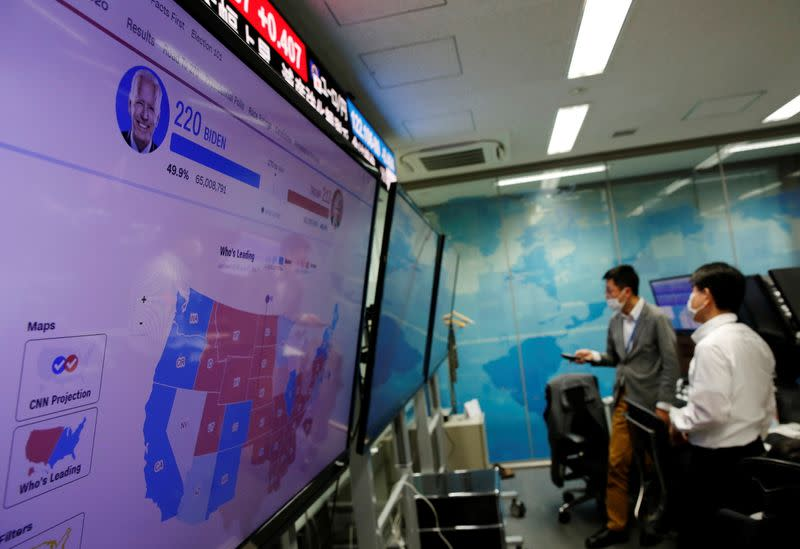 Employees of the foreign exchange trading company Gaitame.com work in front of a monitor showing news on the 2020 U.S. presidential election at a dealing room in Tokyo