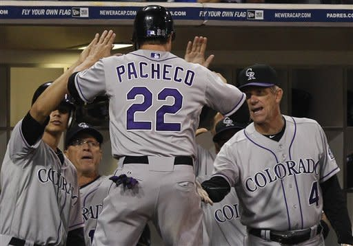 Colorado Rockies' Jordan Pacheco celebrates with teammates after scoring in the 12th inning of the Rockies 8-6 victory over the San Diego Padres during a baseball game Saturday, July 21, 2012 in San Diego. (AP Photo/Lenny Ignelzi)