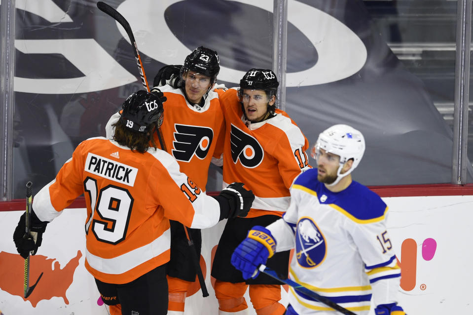 Philadelphia Flyers' Travis Konecny, second from right, celebrates with Oskar Lindblom (23) and Nolan Patrick after Konecny scored a goal past Buffalo Sabres goaltender Carter Hutton during the second period of an NHL hockey game, Tuesday, Jan. 19, 2021, in Philadelphia. (AP Photo/Derik Hamilton)