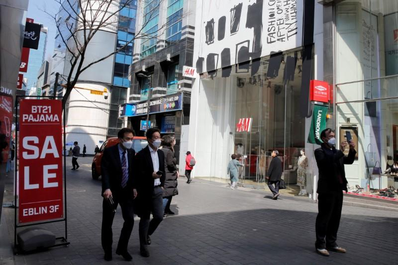 Men wearing masks to prevent contracting coronavirus walk in shopping district in Seoul