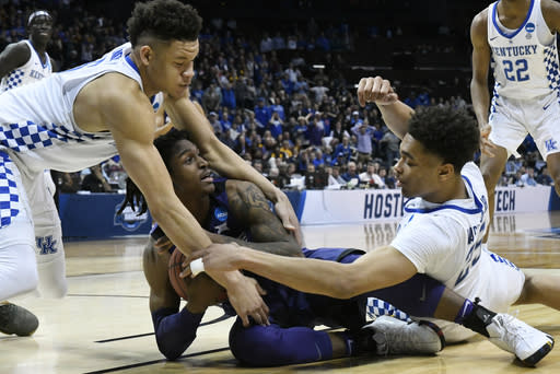 Kansas State guard Cartier Diarra (2) holds onto the ball as Kentucky's PJ Washington (25) and Kevin Knox (5) defend during the second half of a regional semifinal NCAA college basketball tournament game, Friday, March 23, 2018, in Atlanta. Kansas State won 61-58. (AP Photo/John Amis)
