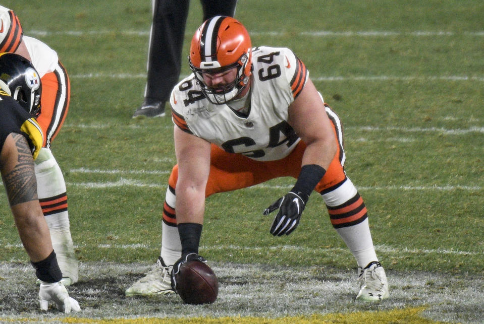 FILE - In this Jan. 10, 2021, file photo, Cleveland Browns center JC Tretter (64) snaps the ball during the first half of an NFL wild-card playoff football game against the Pittsburgh Steelers in Pittsburgh. Following the advice of Browns center and NFL Players Association President Tretter, Cleveland's players joined a list of teams who say they will skip voluntary in-person workouts this offseason. (AP Photo/Don Wright, File)