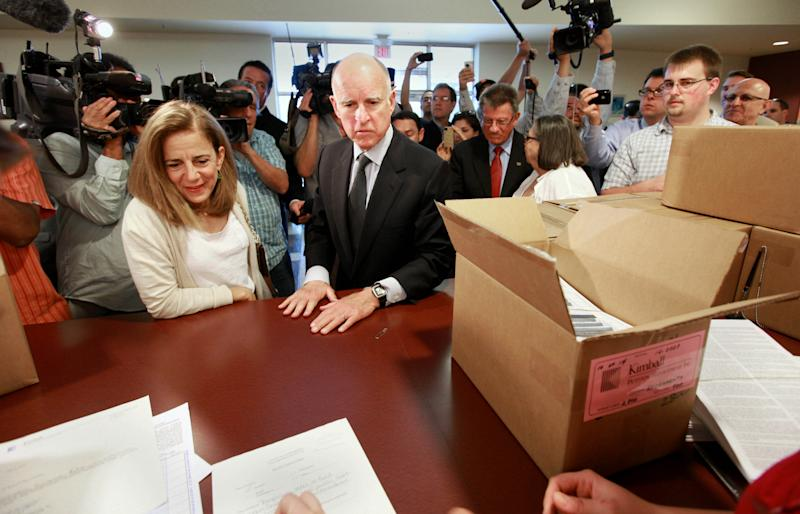 Surrounded by reporters and cameras, Gov. Jerry Brown and his wife, Anne Gust Brown turn in boxes of petitions for his tax-hike initiative at the Sacramento County Registrar of Voters in Sacramento, Calif., Thursday, May 10, 2012. Brown's initiative is one of two tax hike petitions that are expected to qualify for November ballot. Brown has warned that if voters do not pass the tax hikes there would be even deeper cuts to schools, higher education and social services. (AP Photo/Rich Pedroncelli)