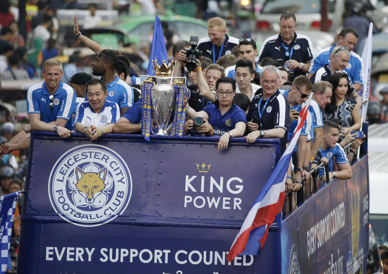 Leicester City players and staff celebrate with the trophy after winning the English Premier League during an open top bus parade through the central business district of Bangkok, Thailand, Thursday, May 19, 2016. The Leicester City team is on a two-day visit to Bangkok to celebrate their premiership win. (AP Photo/Mark Baker)