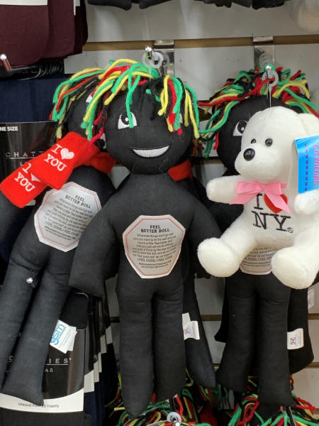 "This undated photo provided by New Jersey state Assemblywoman Angela McKnight shows three ""Feel Better Dolls"" sharing the shelf with a stuffed animal bearing an ""I Love New York"" message at a One Dollar Zone store in Bayonne, N.J. The black rag ""Feel Better"" dolls that came with instructions to ""find a wall"" and slam the toy against it have been pulled from three stores after customers and the lawmaker said they were offensive. (Angela McKnight via AP)"