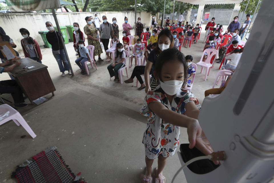 A young girl disinfects her hands before receiving a shot of the Sinovac's COVID-19 vaccine at a Samrong Krom health center outside Phnom Penh, Cambodia, Friday, Sept. 17, 2021. Prime Minister Hun Sen announced the start of a nationwide campaign to give COVID-19 vaccinations to children between the ages of 6 and 11 so they can return to school safely after a long absence due to measures taken against the spread of the coronavirus. (AP Photo/Heng Sinith)