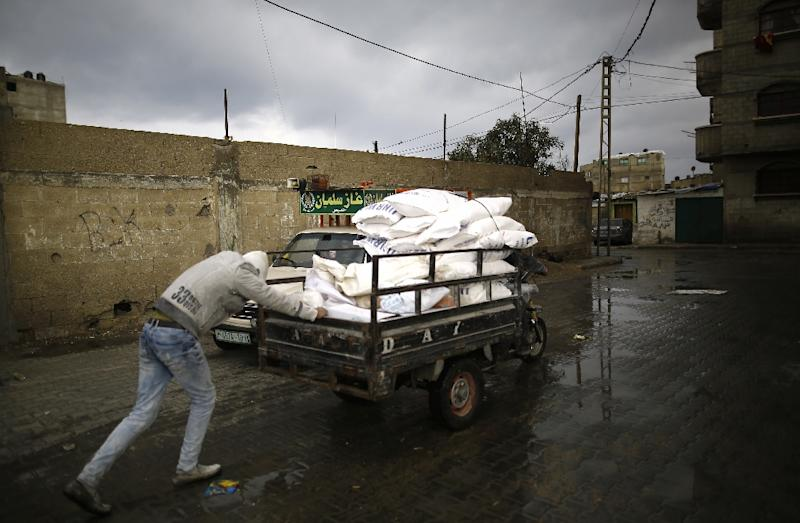 A Palestinian man pushes a cart with food aid in Gaza City on January 17, 2018 (AFP Photo/MOHAMMED ABED)