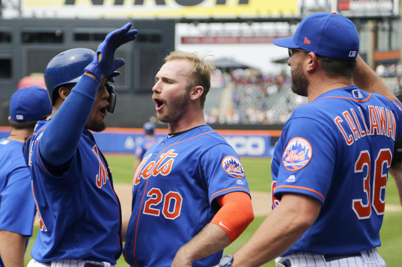 New York Mets' Carlos Gomez, left, is greeted at the dugout by Pete Alonso (20) and manager Mickey Callaway (36) after hitting a three-run home run off Washington Nationals relief pitcher Wander Suero during the eighth inning of a baseball game, Thursday, May 23, 2019, in New York. (AP Photo/Julio Cortez)
