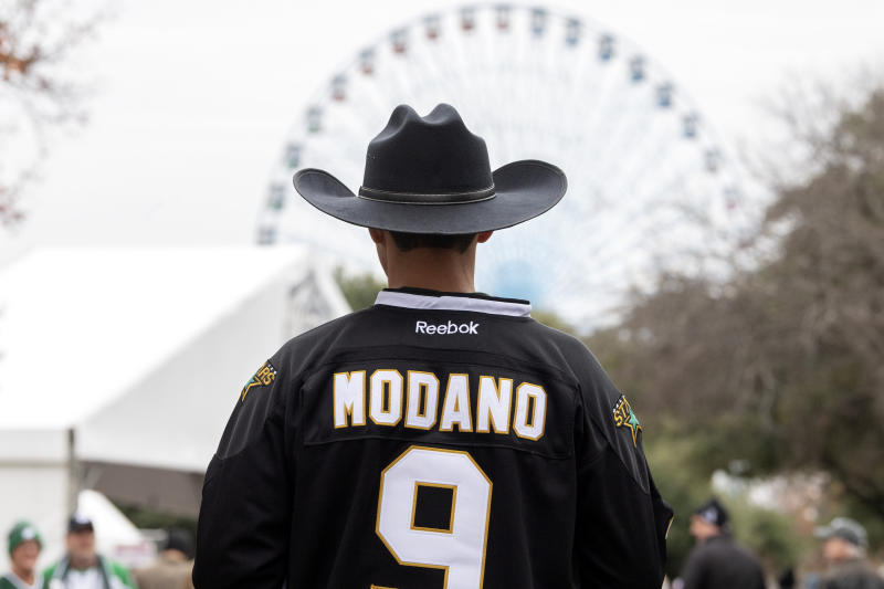 Dallas Stars fan Zac Martinez walks towards Cotton Bowl as the Texas Star ferris wheel rises in the distance before the NHL Winter Classic hockey game between the Dallas Stars and the Nashville Predators at the Cotton Bowl, Wednesday, Jan. 1, 2020, in Dallas. (AP Photo/Jeffrey McWhorter)