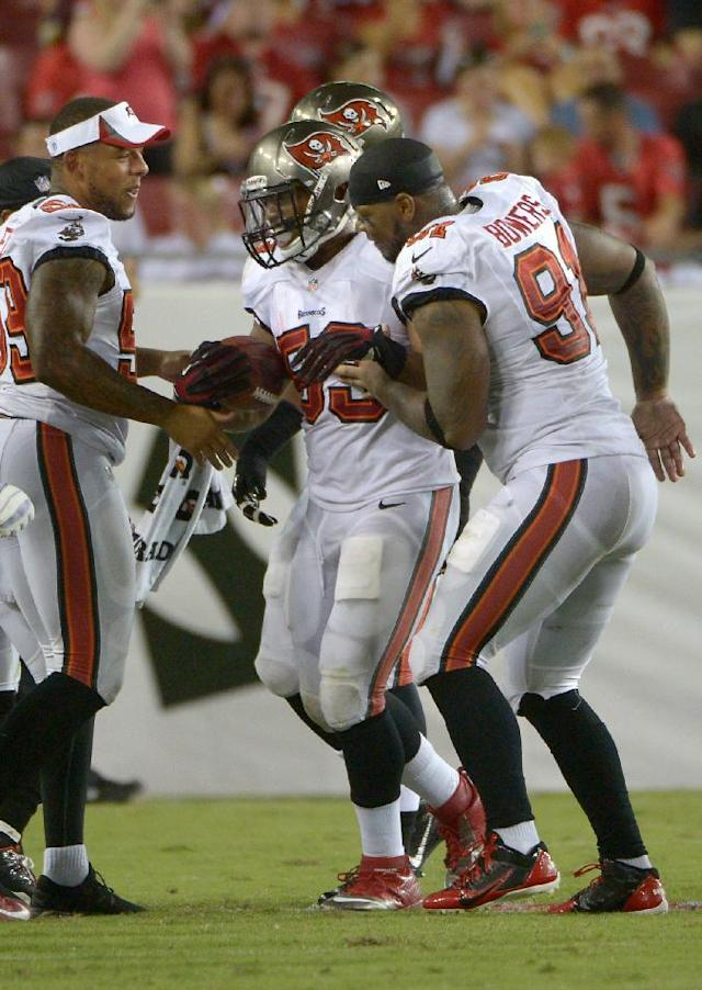Tampa Bay Buccaneers linebacker Najee Goode (53) celebrates with teammates middle linebacker Mason Foster (59) and defensive end Da'Quan Bowers (91) after intercepting a pass by Washington Redskins quarterback Pat White and returning it for a touchdown during the second quarter of an NFL preseason football game Thursday, Aug. 29, 2013, in Tampa, Fla. (AP Photo/Phelan M. Ebenhack)