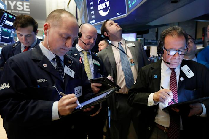 Traders gather at the post that handles Oaktree Capital Group on the floor of the New York Stock Exchange. (AP Photo/Richard Drew)