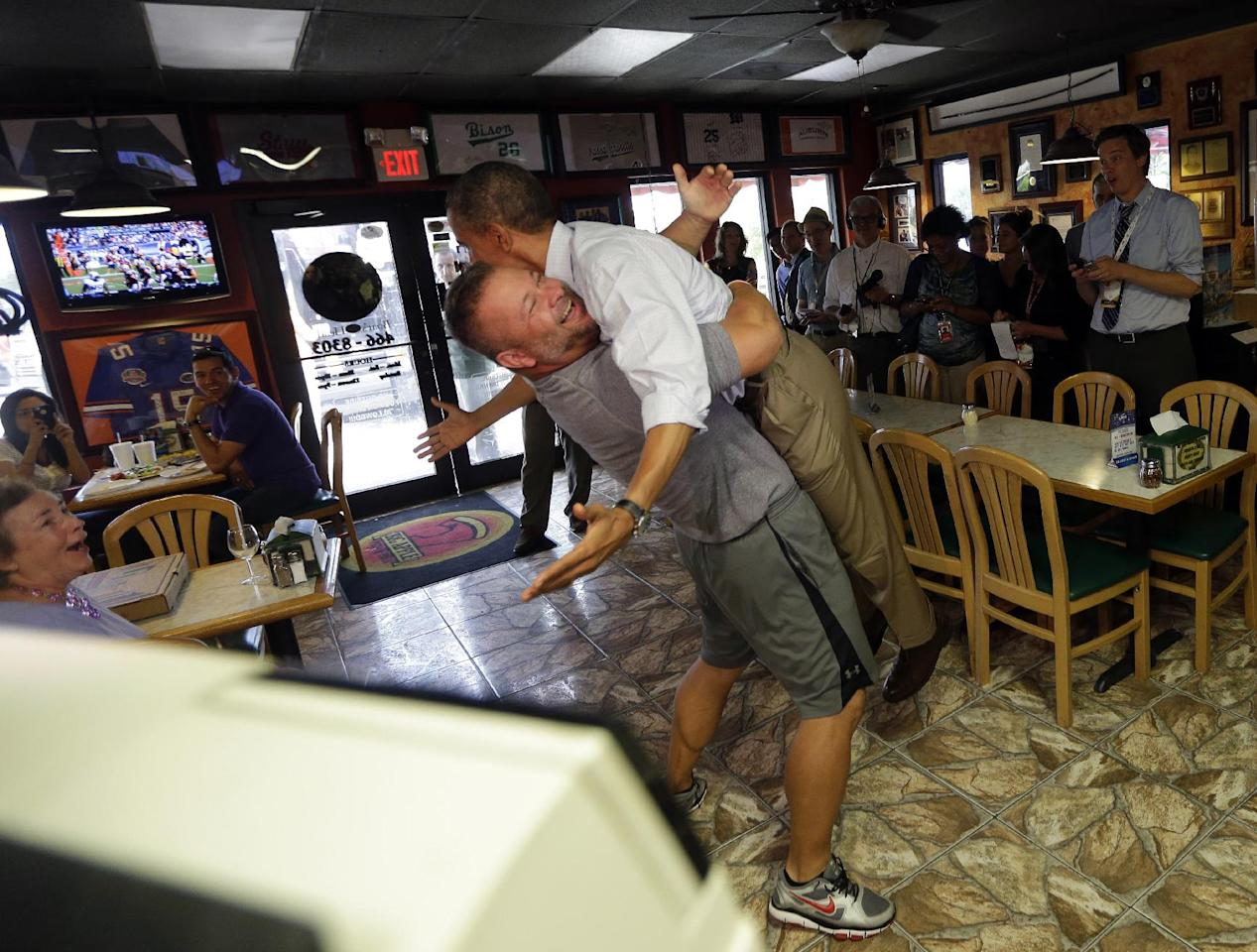 FILE - In this Sept. 9, 2012 file photo, President Barack Obama is picked-up and lifted off the ground by Scott Van Duzer, left, owner of Big Apple Pizza and Pasta Italian Restaurant during an unannounced stop in Ft. Pierce, Fla. Obama goes airborne in a doozie of a bear hug with a pizza guy in Florida. Joe Biden cozies up with a biker chick in Ohio. Even the more reserved Mitt Romney seems to be loosening up some with people he meets on the campaign trail. Kissing babies and slapping backs are so yesterday. The 2012 candidates are putting their all into the campaign cliche of pressing the flesh. (AP Photo/Pablo Martinez Monsivais, File)