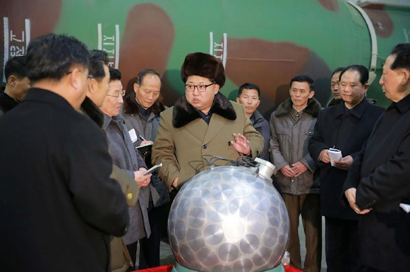 North Korean leader Kim Jong-Un (centre) is shown a miniaturised nuclear warhead which can be fitted on a ballistic missile (AFP Photo/)