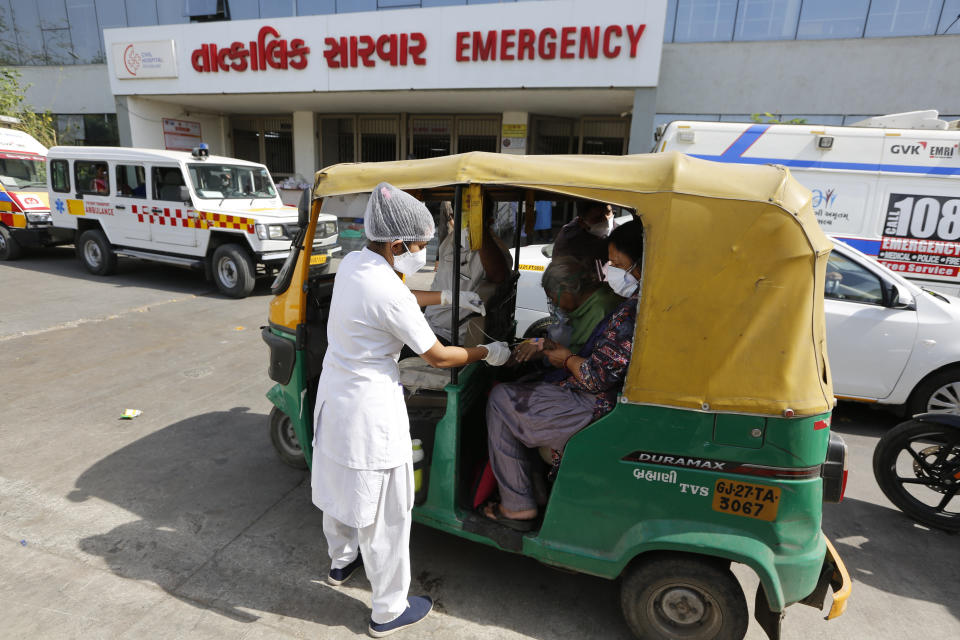 A COVID-19 patient attended by a health worker inside a vehicle at a dedicated COVID-19 government hospital in Ahmedabad, India, Thursday, April 22, 2021. A fire killed 13 COVID-19 patients in a hospital in western India early Friday as an extreme surge in coronavirus infections leaves the nation short of medical care and oxygen. India reported another global record in daily infections for a second straight day Friday, adding 332,730 new cases. The surge already has driven its fragile health systems to the breaking point with understaffed hospitals overflowing with patients and critically short of supplies. (AP Photo/Ajit Solanki)