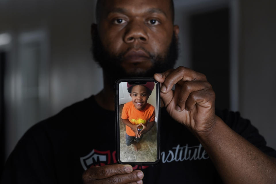 Leon Abdullah El-Alamin shows a photo of his son Leon Jr., in Mt. Morris Township, Mich., Wednesday, Jan. 13, 2021. (AP Photo/Paul Sancya)
